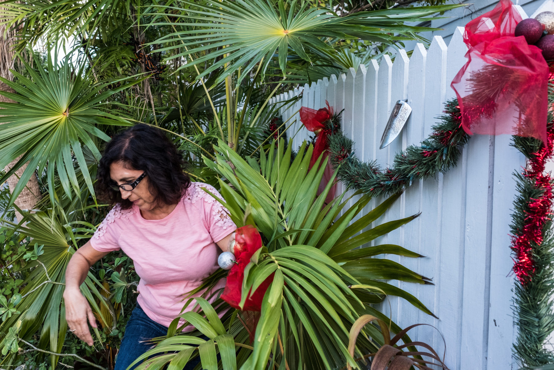 woman hanging christmas decorations in Florida